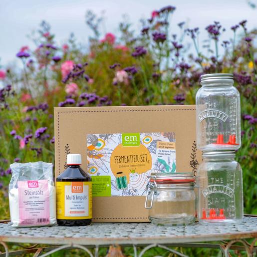 probiotisches Fermentier Set von EM-Chiemgau aufgestellt auf einem Tisch im Garten. Das Set beinhaltet 500g Steinsalz mit Bügelglas, 500ml Multi Impuls Bio-Fermentgetränk, zwei Schraubgläser mit 750ml Fassungsvermögen, zwei Eintauchgitter, einer Anleitung und Umverpackung.